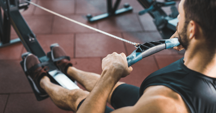 man doing exercise on affordable rowing machine at home