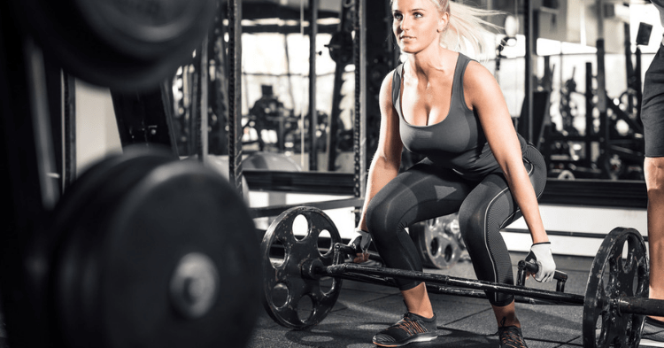 a woman doing trap bar exercises at gym